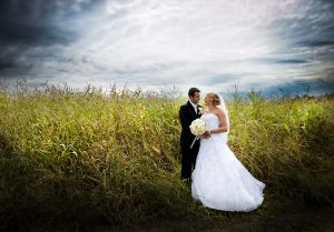 Bride and groom are posing outdoors in a beautiful green field of corn