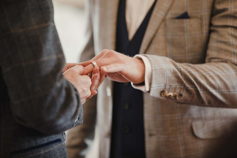 Two men are exchanging rings on their wedding day.